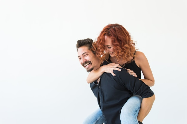 Conceito de pessoas e amor - mulher bonita e bonita sentada nas costas do homem e abraçando-o no branco