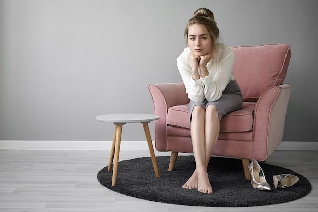 Conceito de pessoas e estilo de vida. bela jovem professora com coque de cabelo relaxando em casa após as palestras na faculdade, sentada descalça na poltrona, olhando para a câmera com expressão facial cansada