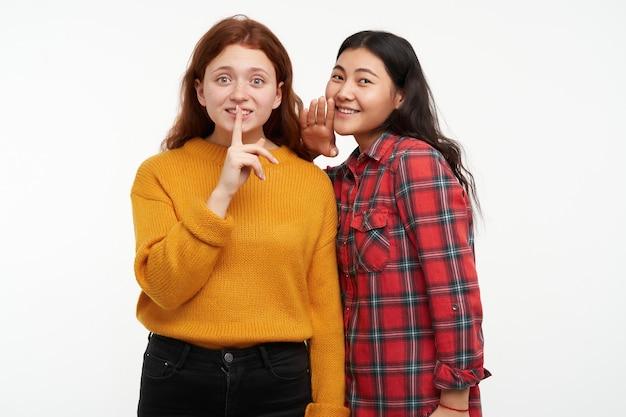 Conceito de pessoas e estilo de vida. dois amigos hipster. menina sussurra para a amiga, mostrando sinal de silêncio. vestindo um suéter amarelo e camisa xadrez. isolado sobre a parede branca