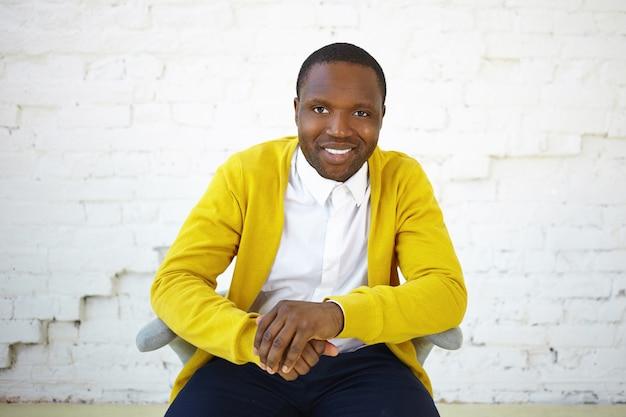 Conceito de pessoas e estilo de vida. foto de estúdio de um jovem afro-americano feliz e positivo, sentado na cadeira e olhando para a câmera com um largo sorriso alegre, mostrando seus dentes brancos perfeitos, apertando as mãos