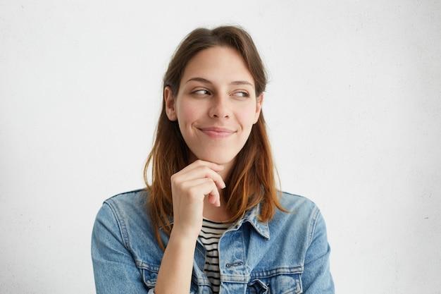 Conceito de pessoas e estilo de vida. foto horizontal de uma garota atraente com um sorriso charmoso e enigmático, segurando a mão em seu queixo e olhando para longe