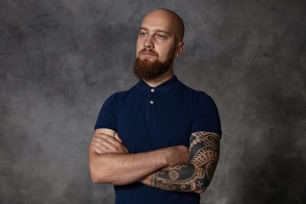 Conceito de pessoas e estilo de vida. homem bonito na moda, isolado, tatuado, com barba difusa e cabeça raspada, posando dentro de casa com os braços cruzados e expressão facial confiante