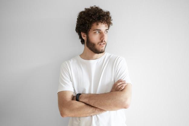 Conceito de pessoas e estilo de vida. retrato de jovem hippie barbudo caucasiano vestindo camiseta branca, posando com os braços cruzados, olhando para longe com uma expressão séria e pensativa
