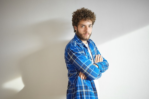 Conceito de pessoas e estilo de vida. retrato de um jovem barbudo elegante, vestido com uma elegante camisa quadriculada, posando com os braços cruzados, com expressão facial séria