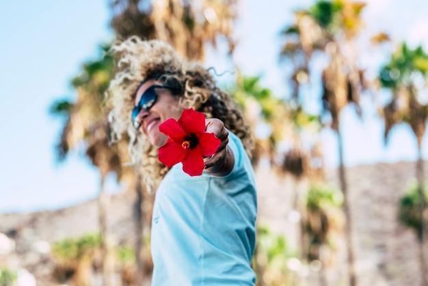 Conceito de pessoas e felicidade com uma bela jovem loira cacheada pulando com uma flor vermelha em foco