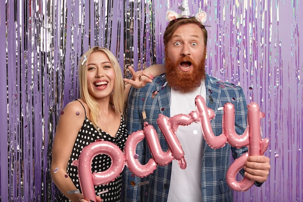 Conceito de pessoas e férias. casal feliz e surpreso segurando balões de ar em forma de letras