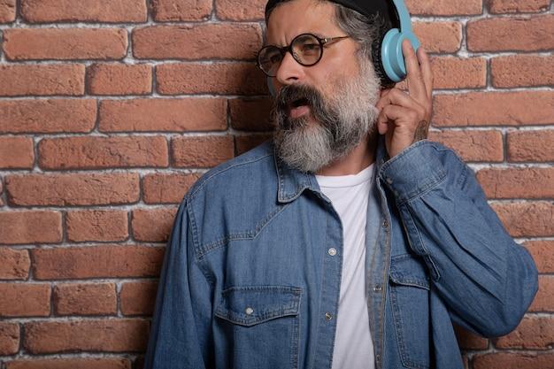 Conceito de pessoas e tecnologia - close-up de um homem barbudo com fones de ouvido, ouvindo música na parede de tijolos. imagem com espaço de cópia