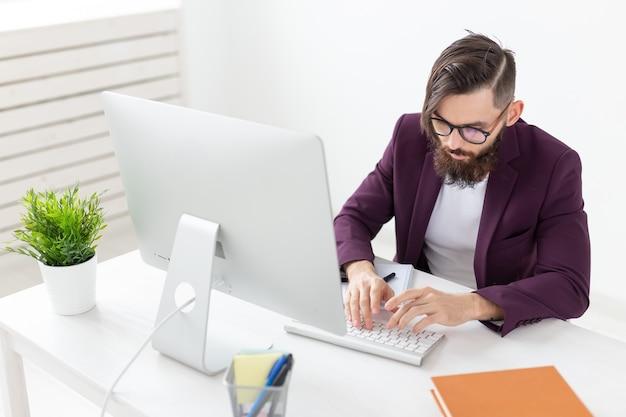 Conceito de pessoas e tecnologia - homem atraente com barba trabalhando no computador