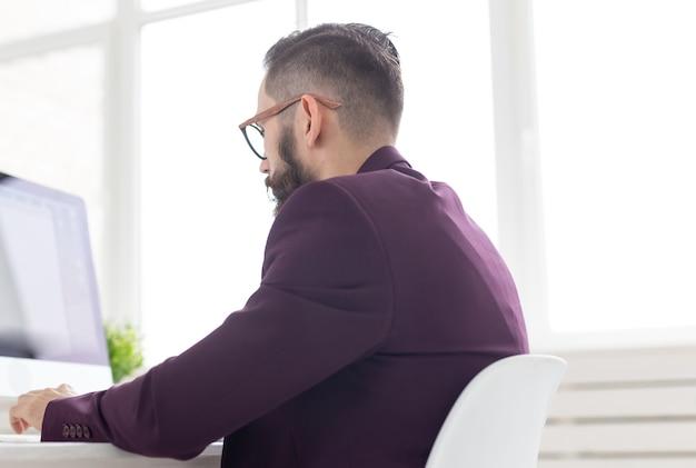 Conceito de pessoas e tecnologia - retrato da vista lateral de um homem bonito vestido com uma jaqueta roxa, trabalhando no computador.