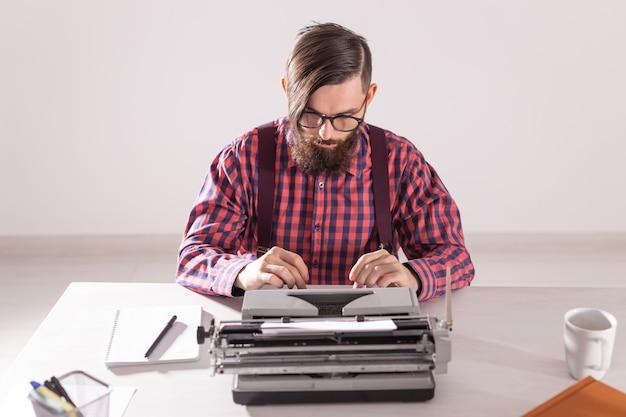 Conceito de pessoas e tecnologia - retrato de um homem barbudo em uma camisa xadrez digitando na parede cinza