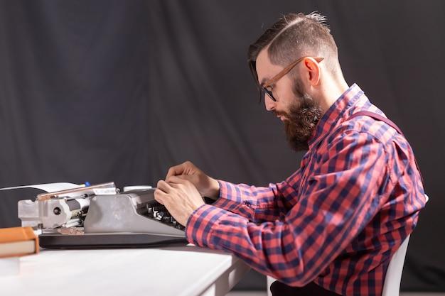 Conceito de pessoas e tecnologia - vista lateral homem bonito com barba trabalhando na máquina de escrever sobre o preto