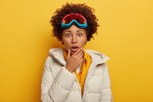 Conceito de pessoas, emoções, hobby e lazer. mulher afro-americana encaracolada emocionalmente assustada usa máscara de snowboard, vestida com um casaco branco fofo, segura o queixo