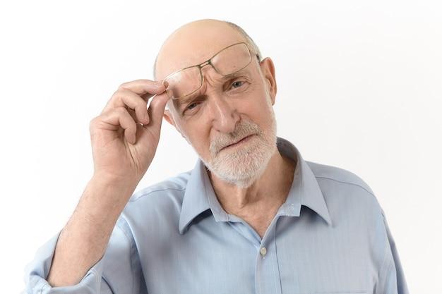 Conceito de pessoas, envelhecimento, óculos, visão e ótica. imagem horizontal de um homem idoso com visão de longo prazo com barba branca tirando os óculos e franzindo a testa para ver claramente o que está à sua frente