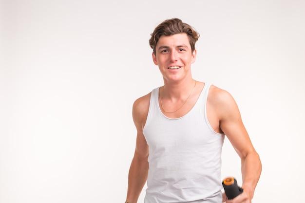 Conceito de pessoas, esporte e fitness - homem musculoso sexy segurando halteres no fundo branco.