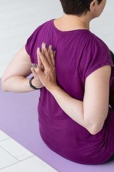 Conceito de pessoas, esporte, ioga e saúde - mulher de meia-idade sentada no tapete de ioga com as mãos atrás das costas close-up