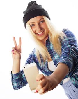 Conceito de pessoas, estilo de vida e tecnologia: muito adolescente usando chapéu, tirando selfies com seu telefone inteligente - isolado no branco