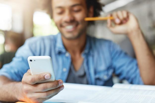 Conceito de pessoas, estilo de vida, tecnologia e comunicação. estudante do sexo masculino, barbudo e bonito, de pele escura, vestindo camisa azul, usando o celular, navegando no feed de notícias nas redes sociais, rindo de memes