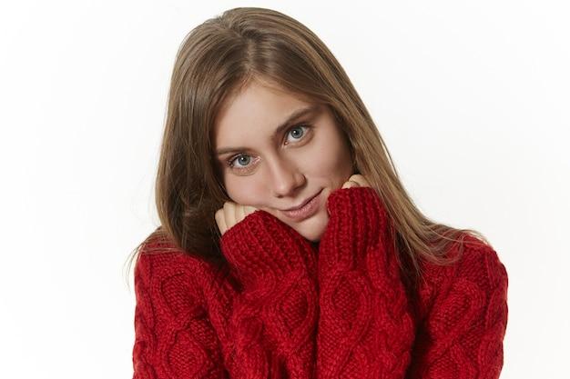 Conceito de pessoas, estilo, moda, beleza, estações e roupas. imagem isolada de uma linda jovem elegante com um sorriso positivo e feliz, vestida com um moderno suéter de malha quente com mangas compridas