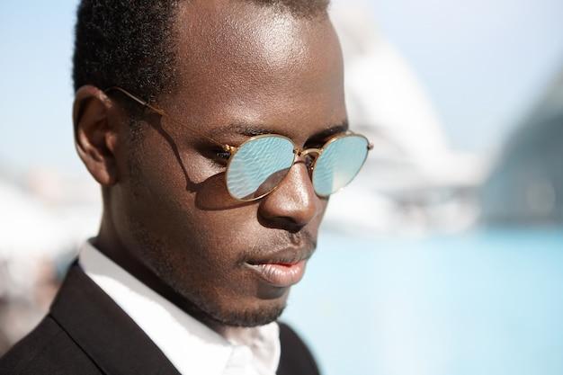 Conceito de pessoas, estilo, moda e negócios. tiro na cabeça do atraente jovem gerente americano africano elegante vestindo terno