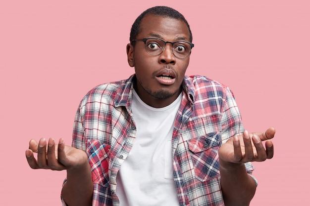 Conceito de pessoas, etnia e incerteza. homem de pele escura hesitante parece surpreso e perplexo para a câmera, sente-se inseguro quanto à tomada de decisão