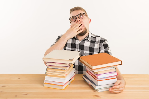 Conceito de pessoas, exame e educação - aluno exausto e cansado, vestido com uma camisa xadrez, sentado à mesa de madeira com muitos livros