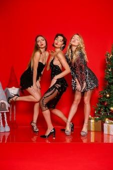 Conceito de pessoas, feriados e glamour - vamos dançar a noite toda! comprimento total de três jovens alegres elegantemente vestidas celebrando o ano novo, o natal, sobre fundo vermelho, posando
