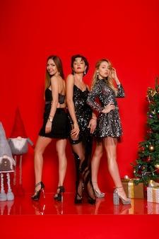 Conceito de pessoas, feriados e glamour - vamos dançar a noite toda! comprimento total de três jovens alegres elegantemente vestidas celebrando o ano novo, o natal sobre fundo vermelho, posando