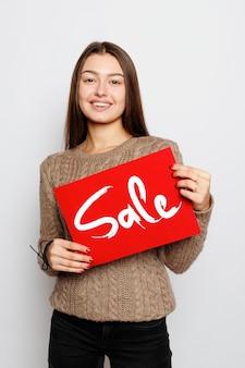 Conceito de pessoas, feriados, venda, compras e propaganda - jovem menina morena sorridente segurando uma placa de venda