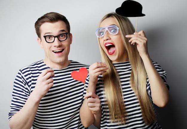 Conceito de pessoas, festa, amor e lazer. lindo casal segurando óculos de festa e chapéu em palitos cinza