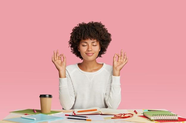 Conceito de pessoas, harmonia e trabalho. mulher de pele escura satisfeita com corte de cabelo afro, medita na área de trabalho, mantém os olhos fechados