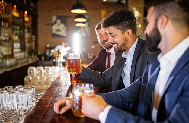 Conceito de pessoas, homens, lazer, amizade e celebração. amigos do sexo masculino felizes bebendo cerveja no bar