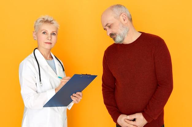 Conceito de pessoas, idade, cuidados de saúde e doença. médica séria de uniforme branco prescrevendo tratamento para seu paciente idoso e barbudo