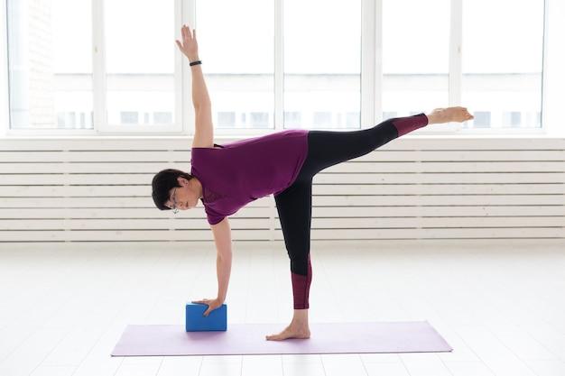 Conceito de pessoas, ioga, esporte e saúde - mulher de meia-idade praticando ioga, usando alongamento