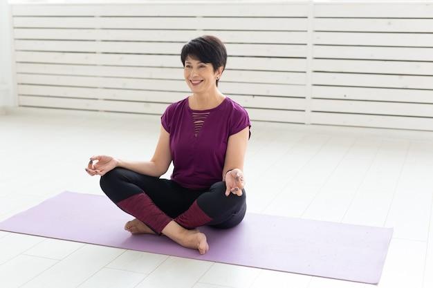 Conceito de pessoas, ioga, esporte e saúde - mulher de meia-idade, sorridente e relaxada, sentada na esteira de exercícios sobre uma superfície branca