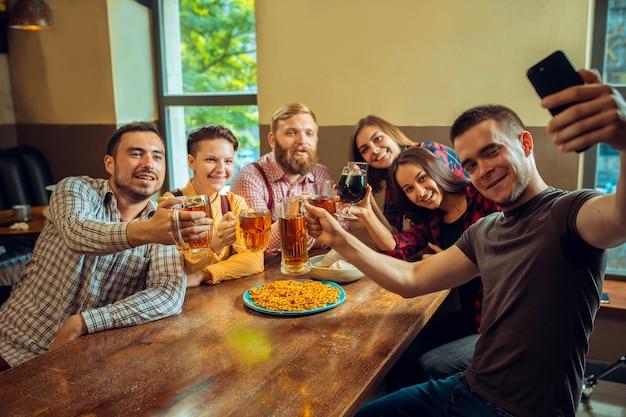 Conceito de pessoas, lazer, amizade e comunicação. amigos felizes bebendo cerveja, conversando e tilintando de copos em bar ou pub e tirando foto de selfie pelo celular.