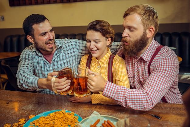 Conceito de pessoas, lazer, amizade e comunicação - amigos felizes bebendo cerveja, conversando e tilintar de copos no bar ou pub