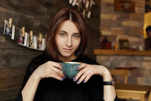 Conceito de pessoas, lazer e estilo de vida. linda menina morena europeia vestida com roupas pretas elegantes, segurando a xícara de chá ou café durante o almoço no restaurante com paredes de madeira e interior acolhedor