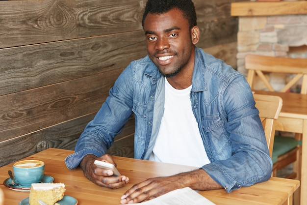 Conceito de pessoas, lazer e tecnologia. jovem atraente de pele escura usando camisa jeans, enviando mensagens no celular enquanto toma um cappuccino e um bolo no café