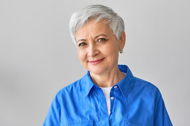 Conceito de pessoas maduras, envelhecimento e beleza. alegre atraente aposentada de meia-idade com cabelo curto e grisalho sorrindo, aproveitando a aposentadoria, passando o dia em casa