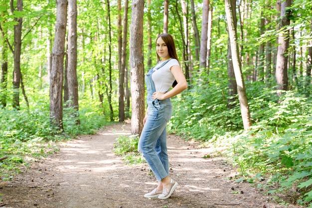 Conceito de pessoas, moda e natureza - retrato de uma mulher jovem e bonita elegante vestida de jeans e camiseta branca.