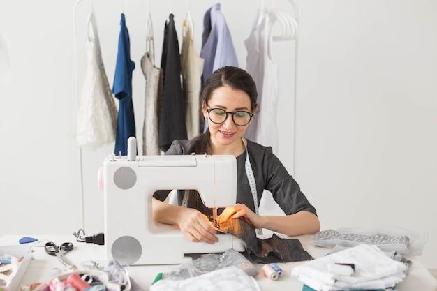 Conceito de pessoas, moda e showroom - jovem estilista costura roupas em uma máquina de costura.