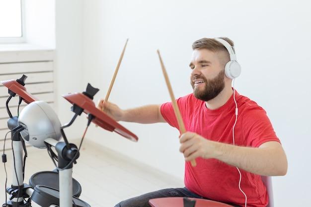 Conceito de pessoas, música e hobby - homem com fones de ouvido brancos tocando bateria sobre fundo claro.