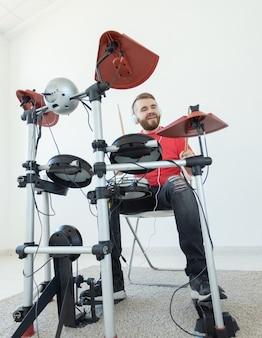 Conceito de pessoas, música e hobby - homem durão em camiseta vermelha e tênis preto tocando bateria eletrônica