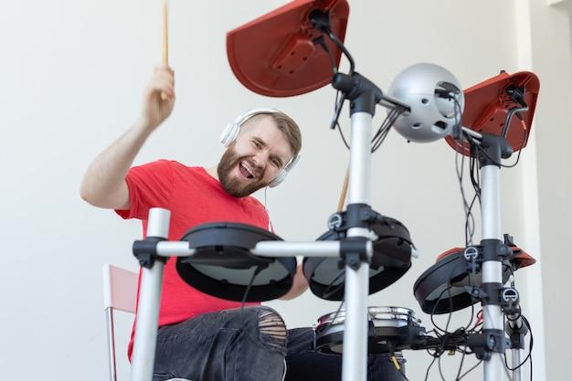 Conceito de pessoas, música e hobby - homem feliz que passa seu tempo livre tocando bateria