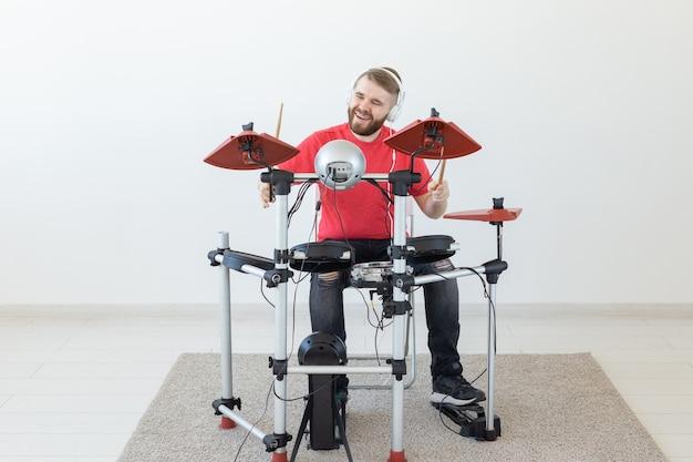 Conceito de pessoas, música e hobby - homem nas horas vagas tocando bateria eletrônica.