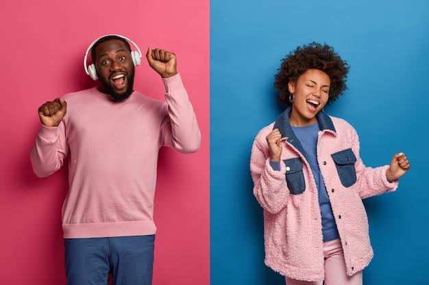 Conceito de pessoas, música e lazer. feliz casal afro-americano dança despreocupado, mova-se ativamente e mantenha as mãos levantadas, ouça música em fones de ouvido, isolado na parede rosa e azul, divirta-se