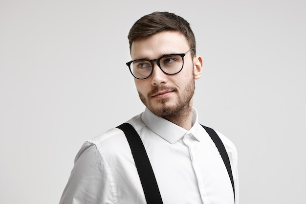 Conceito de pessoas, negócios, estilo, moda e modelagem. jovem modelo europeu barbudo atraente em óculos elegantes e camisa branca elegante com suspensórios posando no estúdio para propaganda