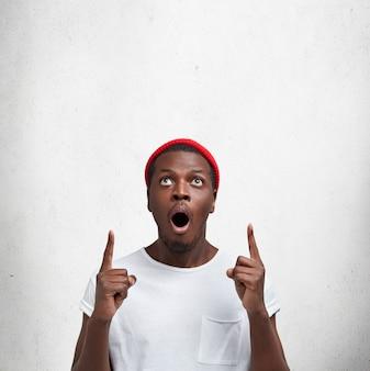 Conceito de pessoas, publicidade e etnia. foto vertical de um homem de pele escura espantado olha para cima e indica com os dedos indicadores para o teto, vê algo inesperado