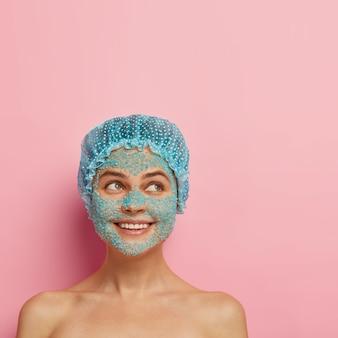 Conceito de pessoas, pureza e tratamento facial. mulher jovem e sorridente satisfeita aplica esfoliante de sal marinho azul, tem corpo nu, pele limpa e brilhante, usa touca de banho, olha de lado, tem procedimento de cosmetologia