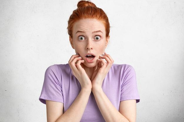 Conceito de pessoas, reação e emoções. mulher ruiva e sardenta surpresa olha para a câmera com olhar surpreso, chocada ao descobrir sobre o fracasso